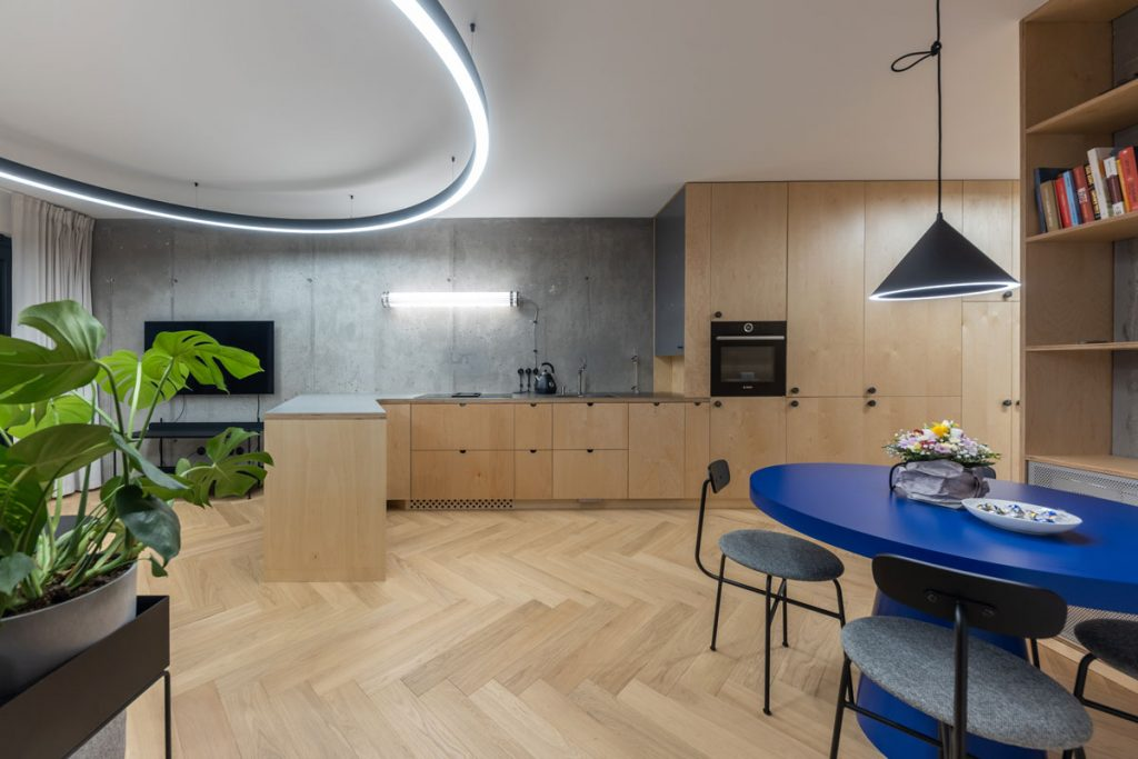 minimalistický industriálny interiér kuchyne spojenej s obývačkou s dizajnovým osvetlením v tvare kruhu a exteriérovým svietidlom nad kuchynskou linkou, dreveným kuchynským nábytkom, modrým dizajnovým stolom s kovovými stoličkami a betónovou stenou