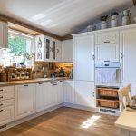 vidiecka kuchyňa v bielej farbe a s tehlovým obkladom v montovanom rodinnom dome
