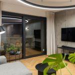 minimalistická industriálna obývačka s východom na terasu, betónovou stenou a hlasovo ovládaným osvetlením