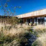 moderná drevostavba v tvare písmena L s udržateľnou prírodnou záhradou s výsadbou z okrasných tráv, kvitnúcich trvaliek a štrkovým chodníčkom vedúcom od terasy domu