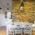 jedáleň vo vidieckom štýle s bielym stolom a stoličkami, tehlovým obkladom na stene a pieckou