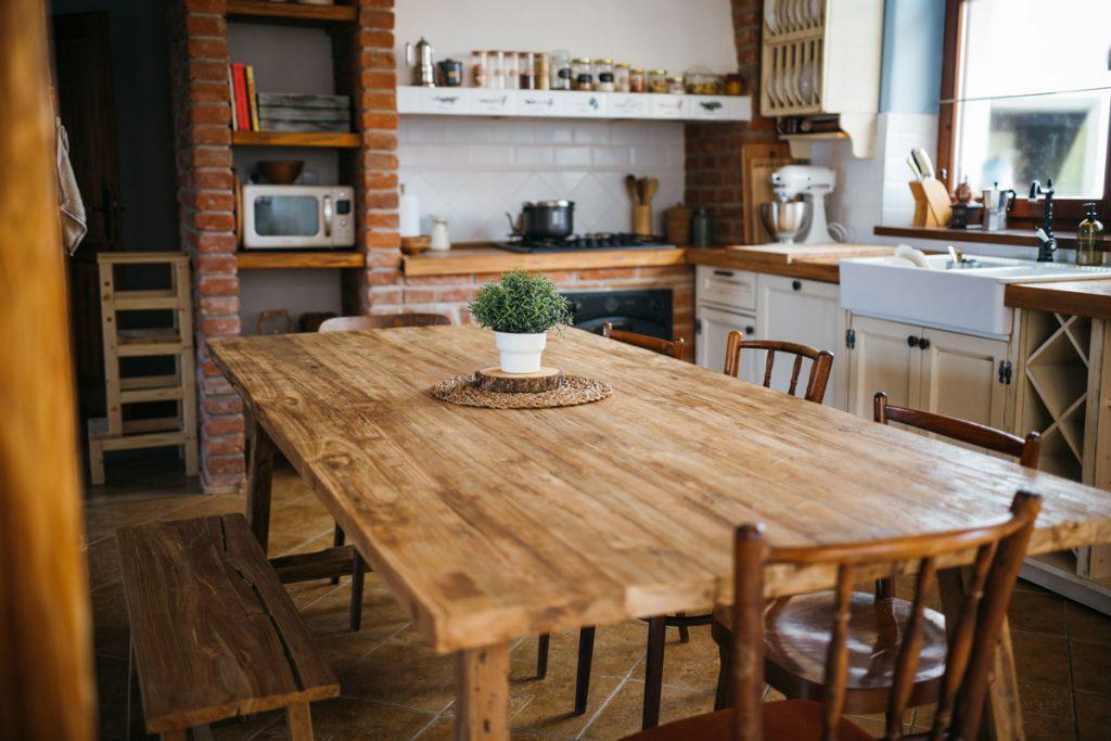 Dom Márie Bartalos: Rustikálna kuchyňa s masívnym stolom a odhalenými tehlami pri kuchynskej linke