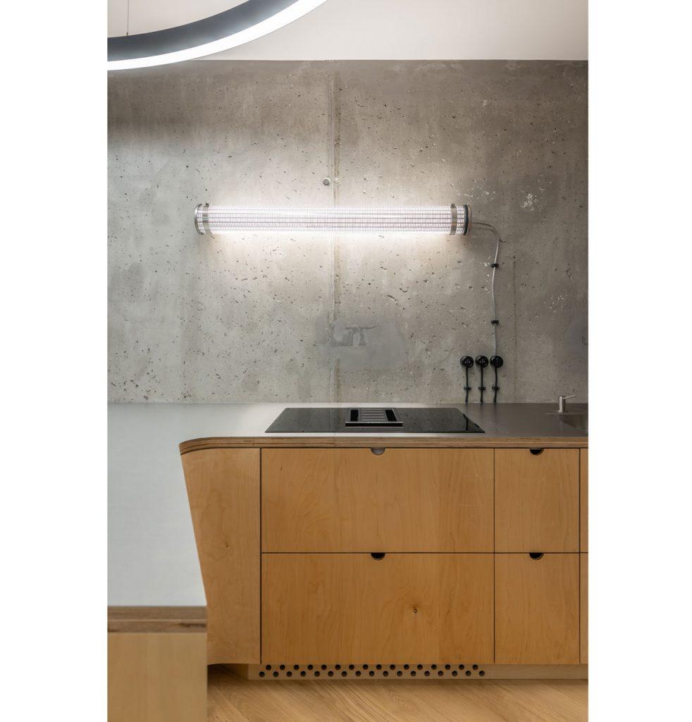 minimalistická drevená kuchynská linka s oblým zakončením a exteriérovým osvetlením na betónovej stene