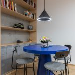 industriálna drevená knižnica na betónovej stene s kovovými perforovanými dvierkami na skrinkách a jedálenský kút s výrazným dizajnovým modrým stolom a kovovými stoličkami
