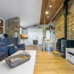 obývačka vo vidieckom štýle, s tehlovým obkladom na stene, pohovkou s dvomi ušiakmi a dekoráciami na drevenej polici a okennými rámami s pletivom