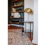 Bývanie Márie Bartalos: kovovo-drevený regál pri tmavozelenej stene a retro lampa na okrúhlom stolíku