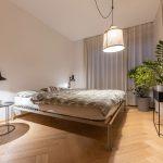minimalistická industriálna spálňa s kovovou posteľou, kovovým nočným stolíkom a zelenými izbovými kvetmi