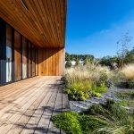 moderná drevostavba rodinného domu s drevenou terasou a trvalo udržateľnou záhradou, tzv. riadenou lúkou