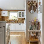 kuchyňa vo vidieckom štýle s bielou kuchynskou linkou, tehlovým obkladom a prírodnými dekoráciami