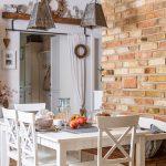 """biely jedálenský stôl vo vidieckom štýle, s kovovými ručne vyrobenými svietidlami visiacimi na jutovom motúze, tehlovou stenou a motívom vidieka v podobe krížikov a """"čokoládiek"""" na nábytku a doplnkoch"""