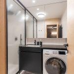 industriálna kúpeľňa s práčkou, čiernou lesklou doskou s umývadlom, čiernou skrinkou a drôtovaným sklom na sprchovacom kúte