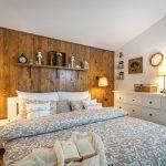 vidiecka spálňa s bielou komodou,, dreveným obkladom na stene za posteľou a závesnými dekoráciami z dreveného rámu, pletiva a kvetín