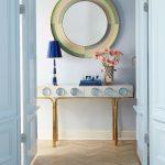 Okrúhle zrkadlo vo farebnom ráme zavesené nad dizajnovým stolíkom