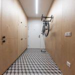 odkladacie priestory v chodbe riešené plynulou plochou skríň vysokých až po strop, s 3D podlahou a bicyklom zaveseným na stene