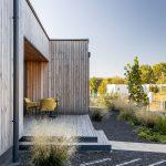 terasa pred vstupom do rodinného drevodomu a okrasná udržateľná záhrada bez trávnika, so štrkovými plochami