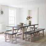 Jedáleň s dreveným obložením stien a drevenou podlahou, s jedálenským stolom s betónovou doskou a lavicami s betónovými doskami.