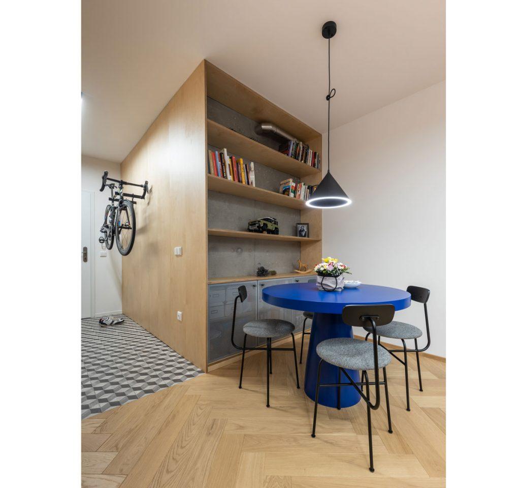 knižnica plynule vychádzajúca zo steny v chodbe, s priznanou rúrou, s betónovým podkladom, otvorenými policami a kovovými dvierkami na skrinkách. vedľa knižnice je dizajnový modrý stôl so stoličkami