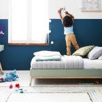 Farebné interiérové trendy: Stena v detskej izbe riešená tmavomodrou farbou v spodnej časti a bielou smerom k stropu