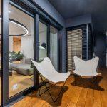 široký balkón s drevenou podlahou a pohodlnými dizajnovými kreslami