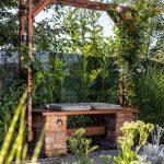 svojpomocne vyrobená záhradná lavička z dreva a tehál, s drevenou konštrukciou okolo ktorej sa ťahá popínavá ruža