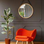 Farebné interiérové trendy: Pomarančové kreslo v kontraste so sivou stenou