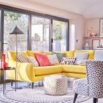 oživenie interiéru: obývačka so žltou sedačkou a vzorovanými vankúšmi, vzorovaným kobercom a taburetkou
