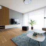priestranná a svetlá moderná obývačka v odtieňoch bielej, hnedej a pastelovej modrej, s dekoračnými drevenými lamelami a tapetami na stene