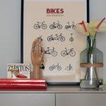 aranžmán s plagátom bicyklov, sklenou vázou s kvetmi a dreveným modelom ruky