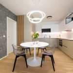 moderná biela kuchyňa vyskladaná zo sektorových prvkov, so zástenou z veľkoformátového gresu s jemným dekorom mramoru a bielym jedálenským stolom s dizajnovými priesvitnými stoličkami a dizajnovým lustrom