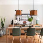 jedáleň s dreveným stolom, čalúnenými stoličkami s drevenými nožičkami a dizajnovými lustrami s dreveným tienidlom