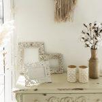 vidiecka komoda, boho rámiky na fotografie, svietniky, váza z jutoviny s bavlníkom a sušené kvety