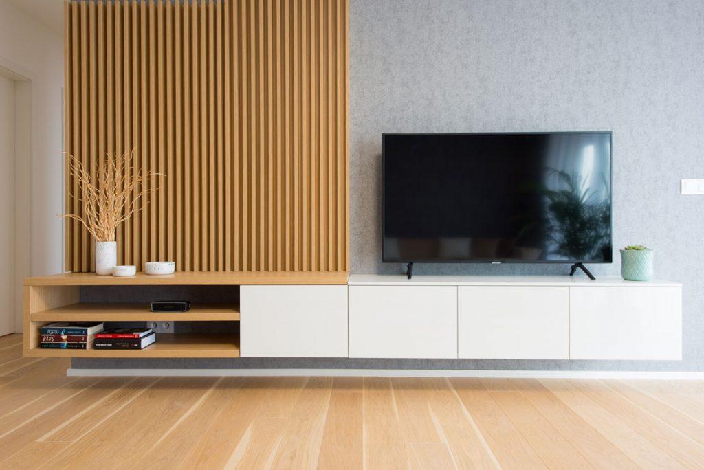 stena v modernej obývačke s dekoratívnym lamelovým dreveným obkladom, tapetou a závesnými skrinkami