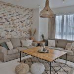 obývačka vo vidieckom boho štýle s dreveným stolíkom s kovovými nožičkami, neutrálnym gaučom, taburetkami a L-kovým stolíkom pripevneným k rohu steny
