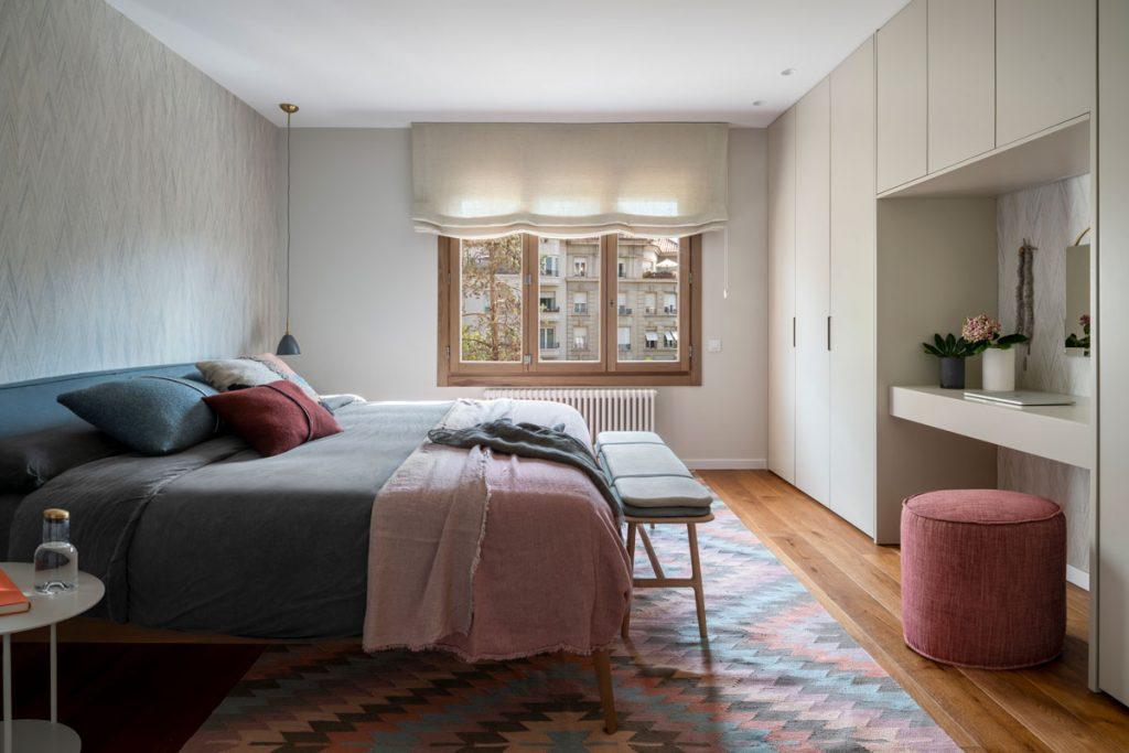 spálňa zariadená v prírodnom štýle a zemitých farbách s manželskou posteľou a toaletným kútikom s taburetkou