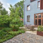átriová záhrada vo vnútrobloku bytového domu s dlažbou, záhradným nábytkom, okrasnou zeleňou, vyvýšeným záhonom a prvkami z cortenu