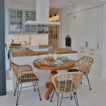 kuchyňa s jedálňou vo vidieckom štýle s boho prvkami, s pastelovo modrou kuchynskou linkou, ostrovčekom, vstavanými skriňami a masívnym dreveným stolom s ratanovými stoličkami