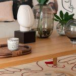 dekorácie na stolíku v obývačke s motívom tváre a sklenenými nádobami s kvetinami