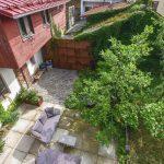pohľad zhora do átriovej záhrady so zeleňou, dlažbou, sedením a cortenovou bránou