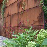 Cortenová brána s trvalkovými záhonmi a popínavými rastlinami