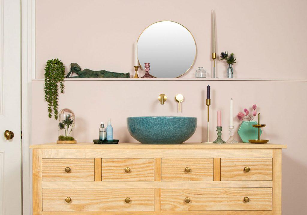 kúpeľňa so skrinkou, modrým umývadlom a dekoráciami
