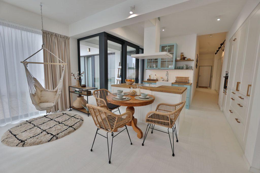 interiér otvorenej kuchyne s prvkami vidieka a boho štýlu, v bielej farbe, s modrou kuchynskou linkou, bielym ostrovčekom a východom na terasu