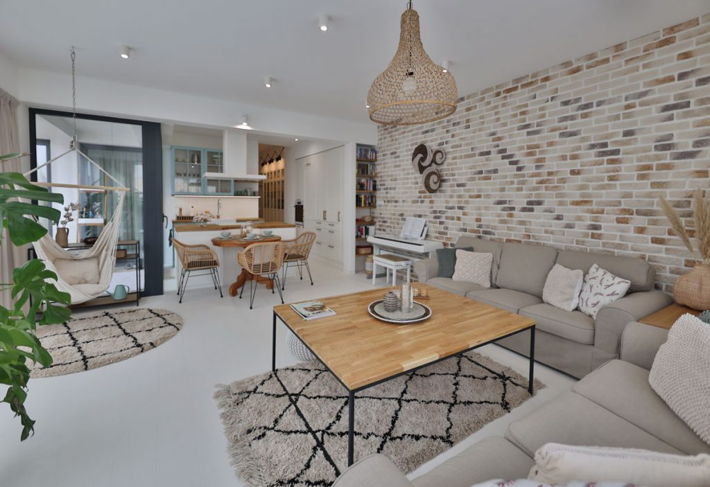 obývačka vo vidieckom štýle, s tehlovým obkladom na stene a konceptom otvoreného priestoru s kuchyňou