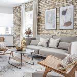 prírodný interiér obývačky so svetlošedou sedačkou, ratanovými kreslami, zvieracou kožou na podlahe a tehlovou stenou