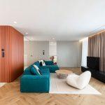 apartmán Sone Skoncovej s obkladom z oblých drevených lamiel, modrou sedačkou, oblým bielym kreslom a pastelovými farbami