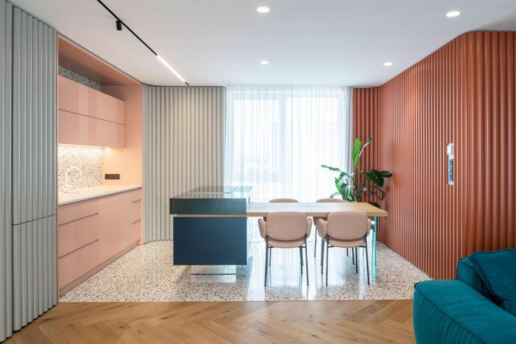 Kuchyňa s terazzom na podlahe a kuchynskej zástene, s obkladom z oblých drevených lamiel na stene, lososovou kuchynskou linkou a ostrovčekom spojeným s jedálenský stolom
