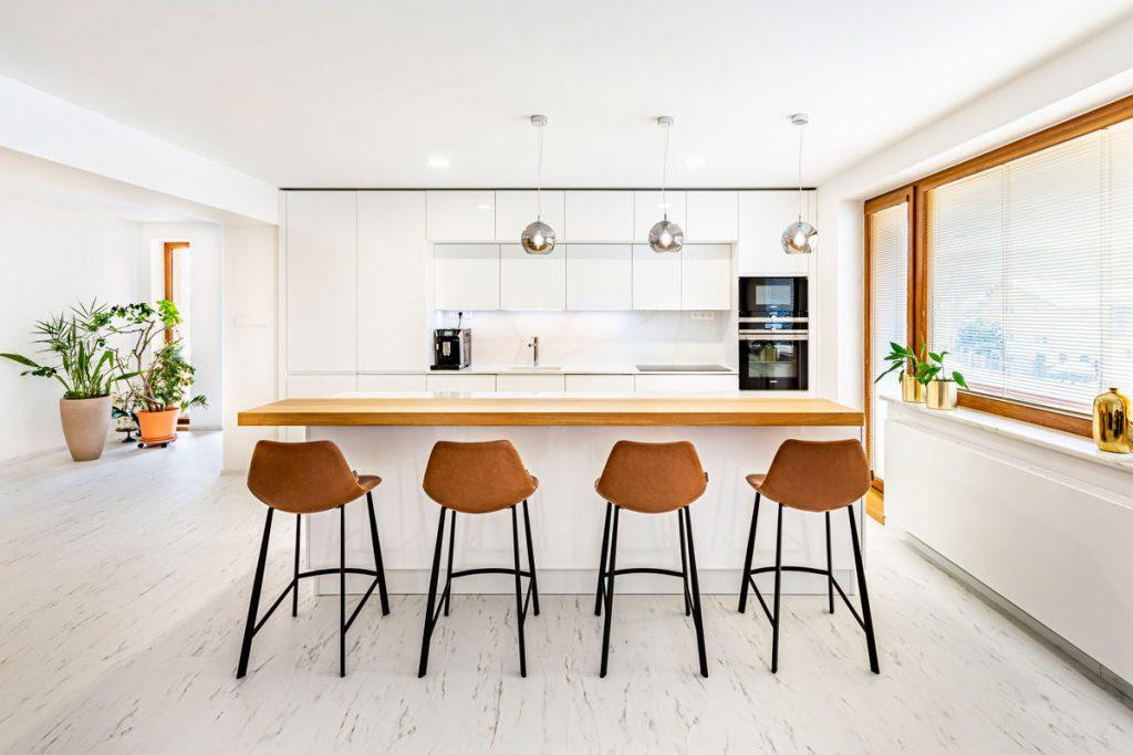 Moderná kuchyňa v bielej farbe s koženými barovými stoličkami