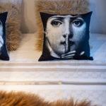 detail vankúšov s motívom tváre na posteli