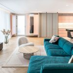interiér apartmánu v pastelových farbách, s obkladom z drevených lamiel, modrou rohovou sedačkou a terazzom na podlahe a kuchynskej zástene