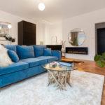 obývačka s modrou sedačkou, ktorá slúži aj na rozdelenie obývacej a jedálenskej zóny