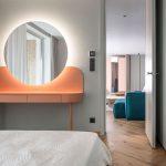 """Detail spálne s okrúhlym podsvieteným zrkadlom """"posadeným"""" do pastelového nočného stolíka"""